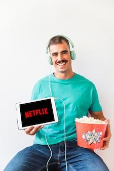 Hombre alegre con palomitas mostrando el logo de netflix