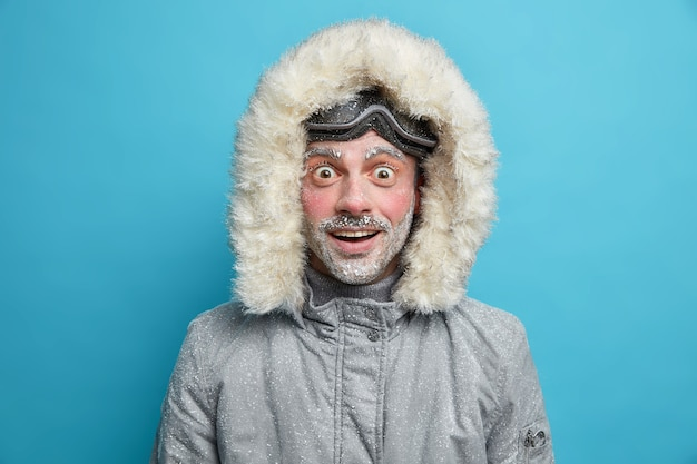 El hombre alegre conmocionado emocional usa chaqueta de invierno tiene la cara roja cubierta de hielo no puede creer en noticias asombrosas.