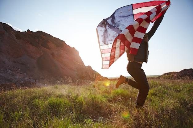 Hombre alegre corriendo con bandera de estados unidos