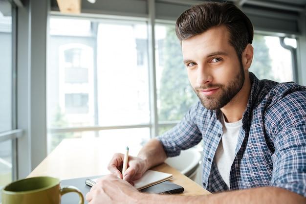 Hombre alegre en coworking de oficina mientras escribía notas