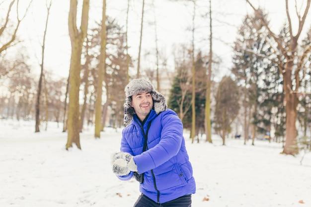 Hombre alegre disfruta de la nieve en el parque, arroja nieve en invierno