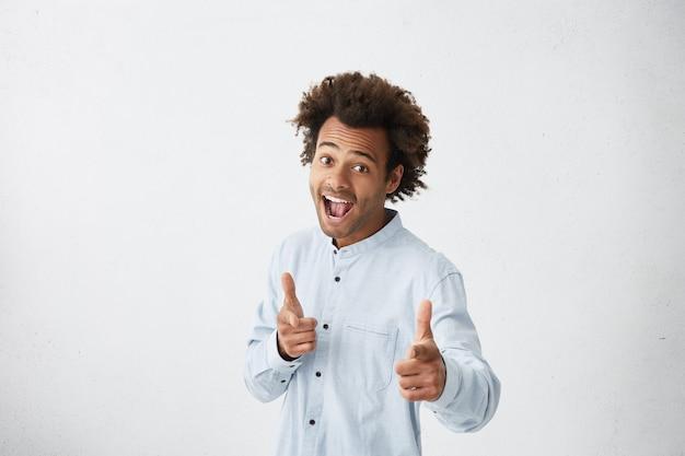 Hombre alegre emocionado con camisa azul claro levantando las cejas y exclamando