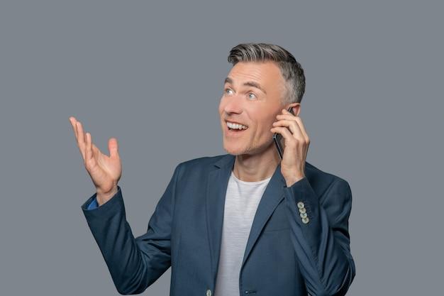Hombre alegre emocional hablando por teléfono inteligente