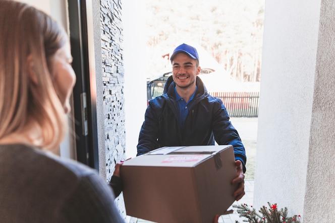 Hombre alegre en el porche con el correo