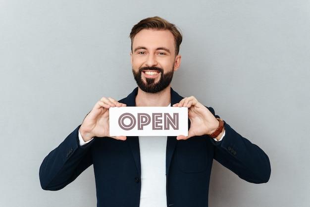 Hombre alegre feliz que sostiene la placa de identificación abierta aislada