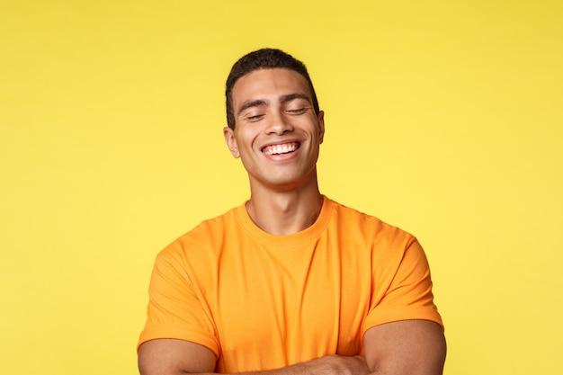Hombre alegre guapo en camiseta, riendo con los ojos cerrados