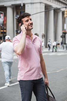 Hombre alegre hablando en teléfono inteligente en la calle