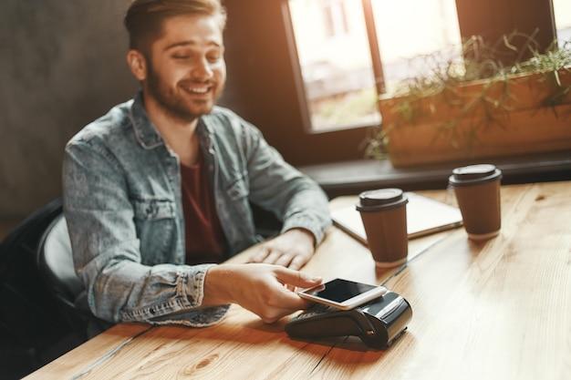 El hombre alegre de manera segura en la cafetería está haciendo un pago con teléfono inteligente sin contacto