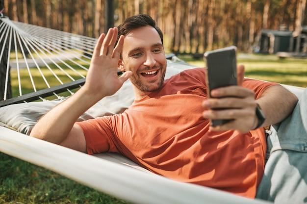 Hombre alegre mirando la pantalla del teléfono inteligente