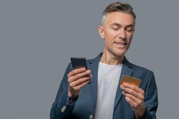 Hombre alegre mirando tarjeta de crédito