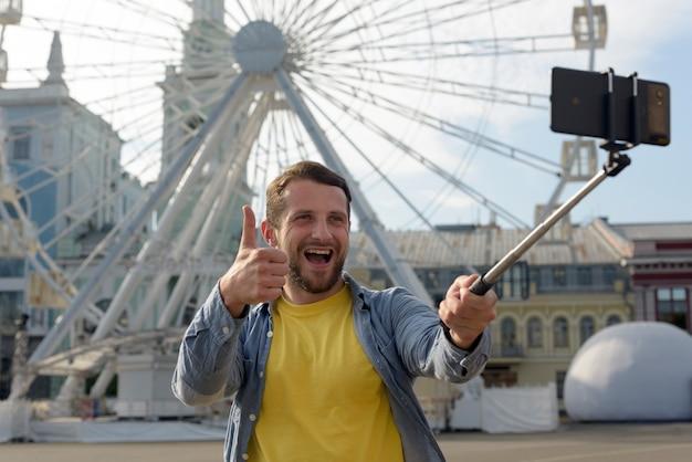 Hombre alegre mostrando pulgar arriba gesto mientras toma selfie delante de la noria