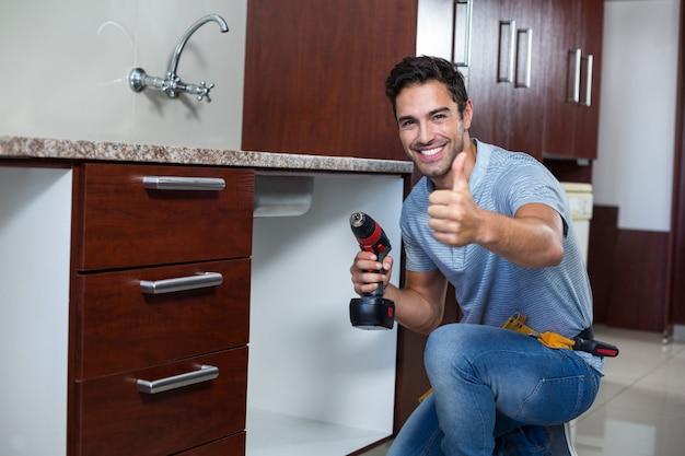 Hombre alegre mostrando los pulgares hacia arriba mientras usa el taladro de mano inalámbrico