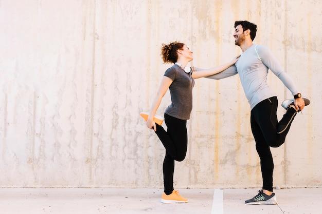 Hombre alegre y mujer haciendo ejercicio juntos