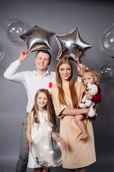 Hombre alegre y mujer pelirroja sosteniendo globos y posando con dos adorables niños