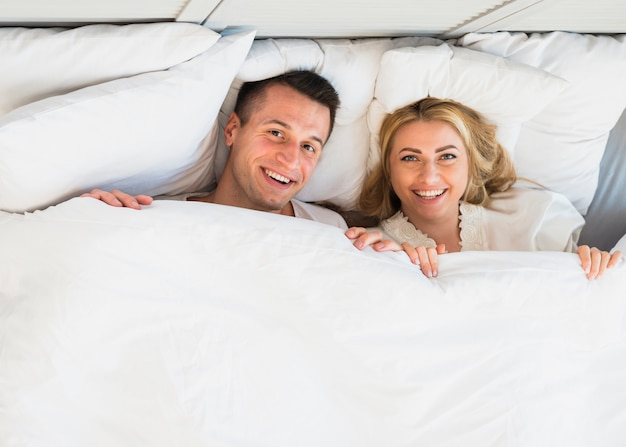 Hombre alegre y mujer sonriente joven debajo de la manta
