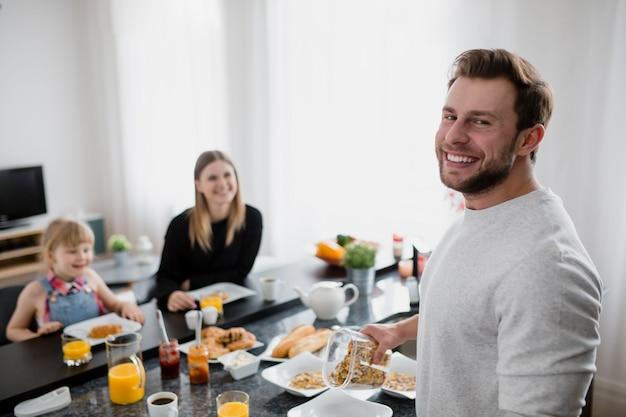 Hombre alegre que cocina el desayuno para la familia