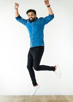 Hombre alegre que salta para arriba aislado en el fondo blanco
