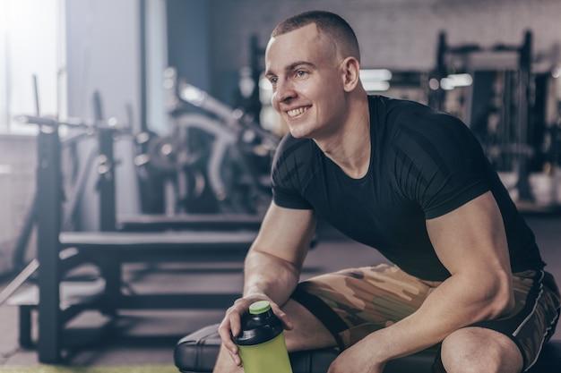 Hombre alegre relajante después de hacer ejercicio en el gimnasio.