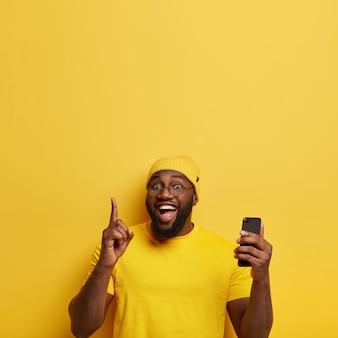 El hombre alegre señala el dedo índice arriba, el propio blog de los creadores, navega por las redes sociales en el teléfono inteligente, tiene expresión facial encantada