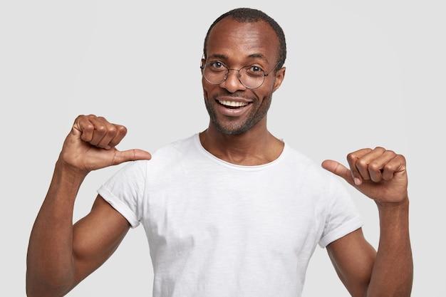 El hombre alegre se señala a sí mismo con ambos pulgares, feliz de comprar ropa nueva, tiene una amplia sonrisa, se para contra la pared blanca