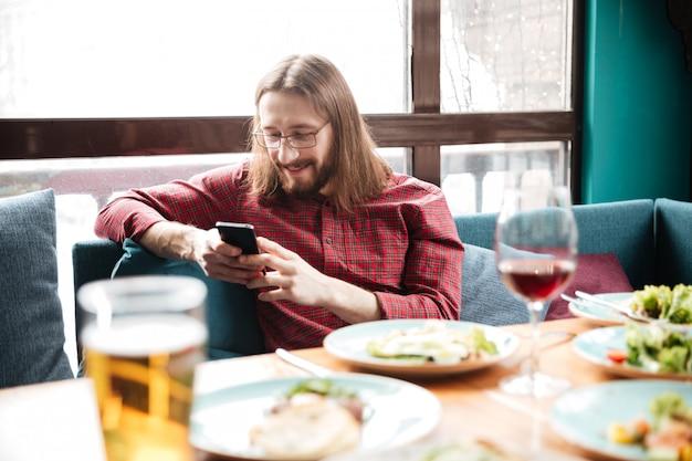 Hombre alegre sentado en la cafetería mientras usa el teléfono móvil.