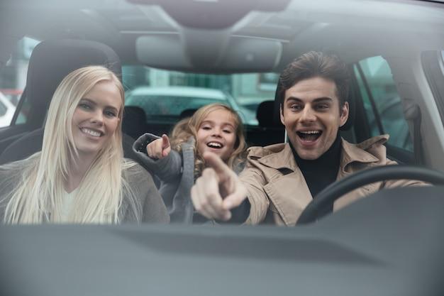 Hombre alegre sentado en coche con su esposa e hija