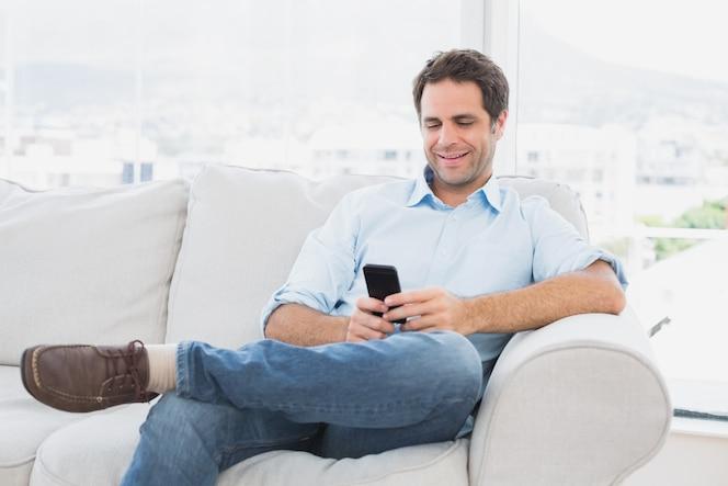 Hombre alegre sentado en el sofá con su teléfono inteligente
