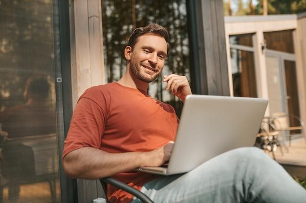 Hombre alegre sentado con portátil al aire libre