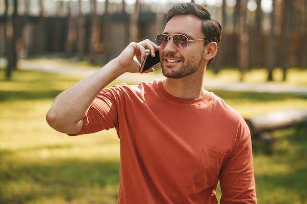 Hombre alegre con smartphone cerca de la oreja al aire libre