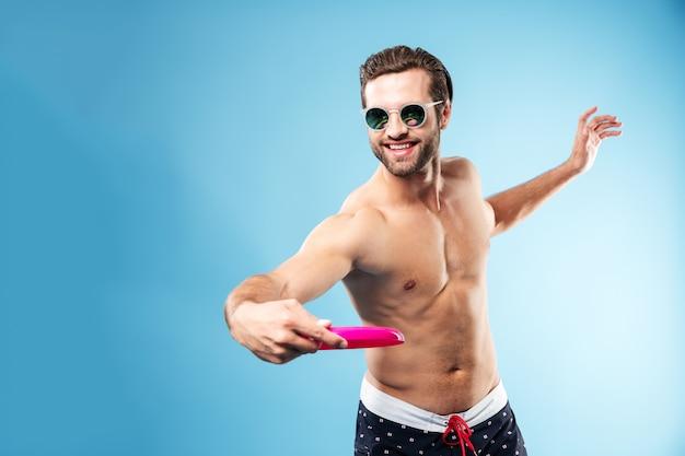 Hombre alegre sonriente en pantalones cortos de verano jugando frisbee