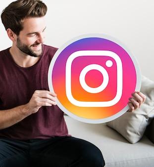 Hombre alegre sosteniendo un ícono de instagram