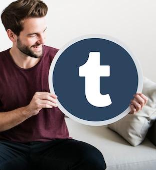 Hombre alegre sosteniendo un icono de tumblr
