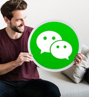Hombre alegre sosteniendo un ícono de wechat