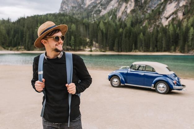 Hombre alegre sosteniendo su mochila y posando con una sonrisa de pie frente al hermoso lago en la montaña