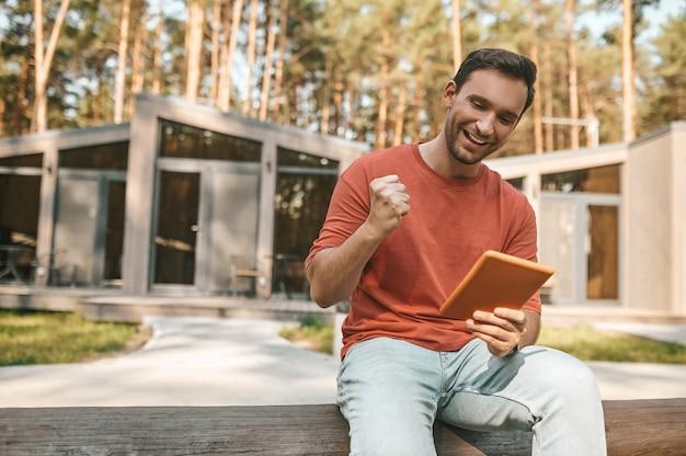 Hombre alegre con tableta gesticulando con puño