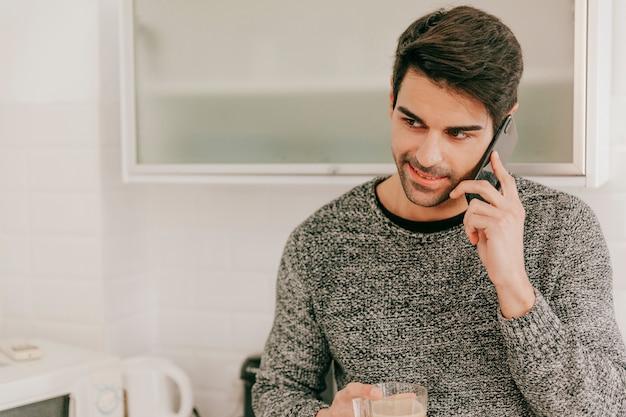 Hombre alegre con taza hablando por teléfono