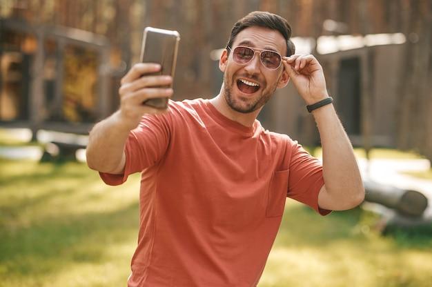 Hombre alegre tomando selfie en smartphone