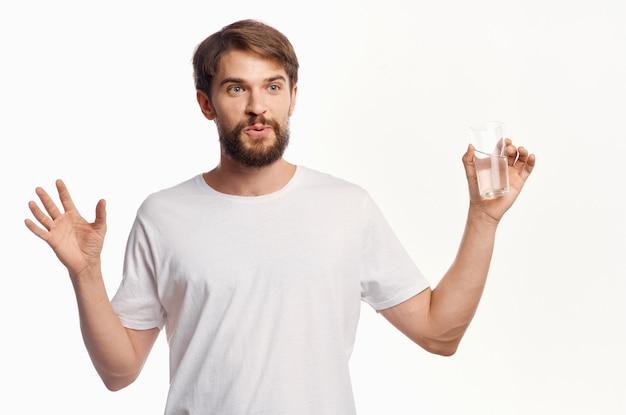 Hombre alegre con un vaso de agua camiseta blanca fondo claro estilo de vida gesticulando con las manos