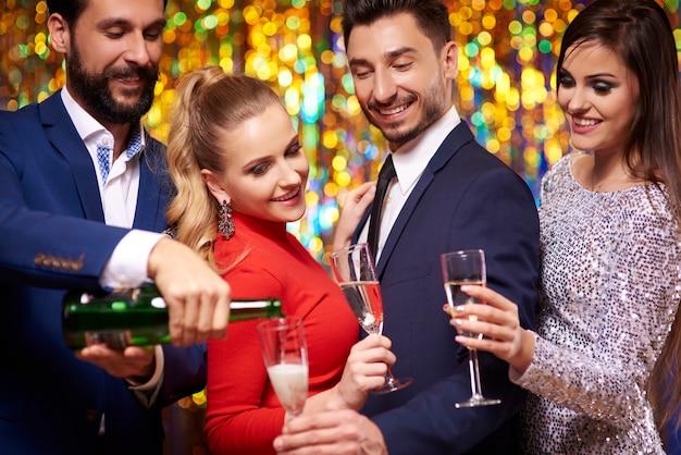 Hombre alegre vertiendo champán para sus amigos