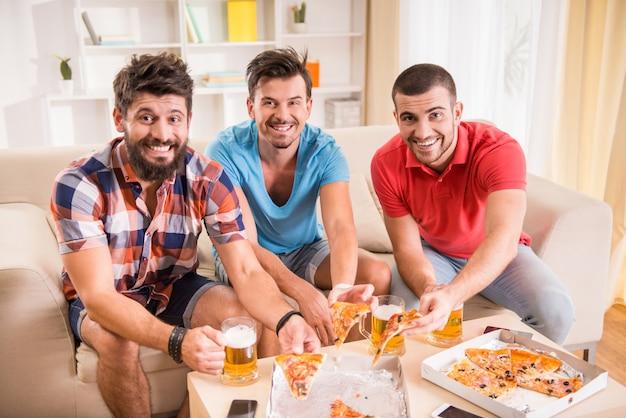 Hombre alegre viendo fútbol en casa y comiendo.
