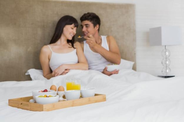 Hombre alimentando cereales para el desayuno a la mujer en el dormitorio