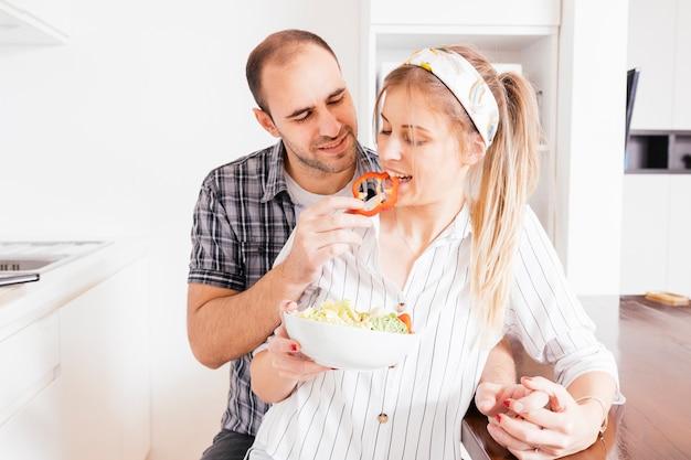Hombre alimentando ensalada a su esposa en la cocina