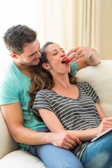 Hombre alimentando una fresa a mujer en sofá