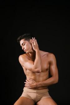 Hombre alisar el cabello con la mano y abrazando el cuerpo