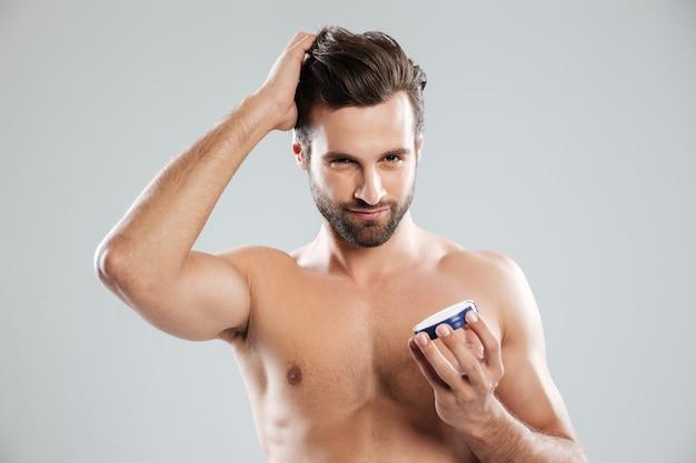 Hombre alisar el cabello y sosteniendo crema aislado