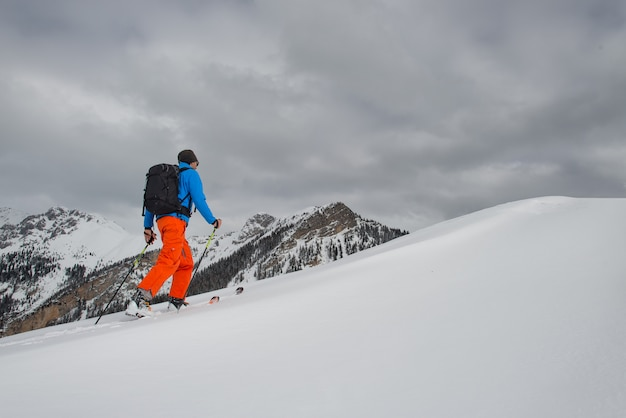 Hombre con alpinismo de esquí subir hacia la cumbre