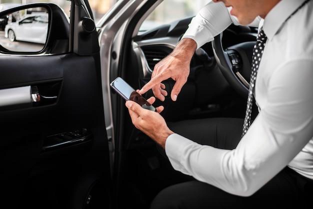 Hombre de alto ángulo dentro del coche comprobando móvil