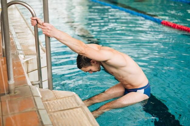 Hombre de alto ángulo en las escaleras de la piscina