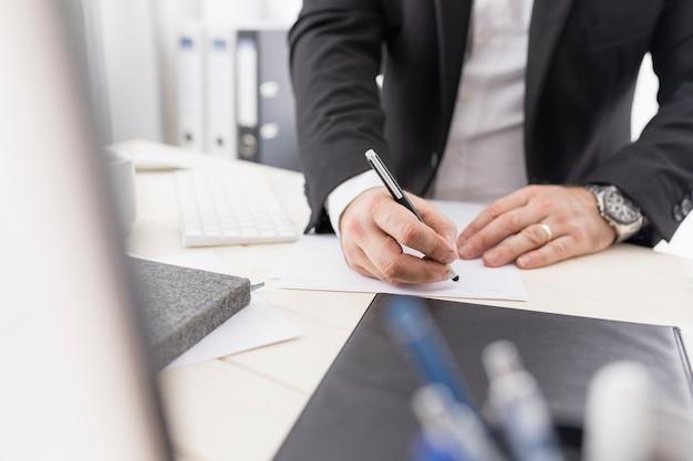 Hombre de alto ángulo escribiendo algo para el trabajo