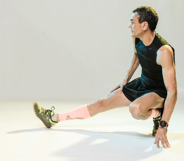 Hombre de alto ángulo estiramiento antes de hacer ejercicio